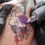 Tattoo artist applies tattoo to arm. She is filling with purple color the tattoo