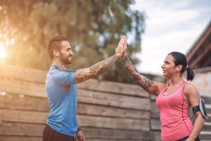 Fit couple with tattoo sleeve resting after jogging.